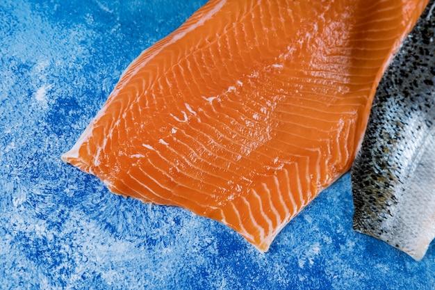 Pezzo crudo di color salmone con degli ingredienti sulla tavola