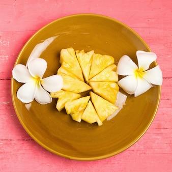 Pezzo di ananas sul piatto con fiore su legno rosa