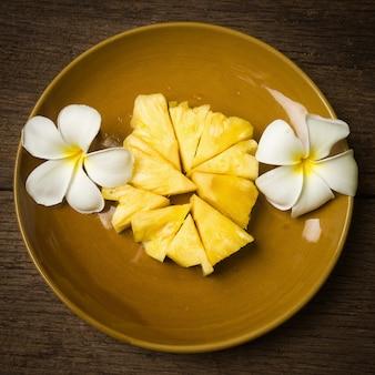 Pezzo di ananas sul piatto con fiore su legno vecchio