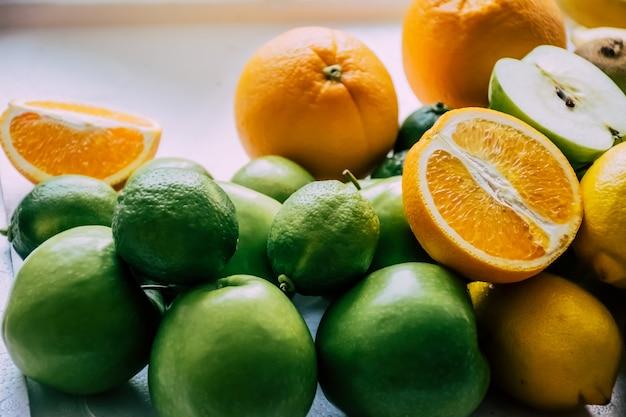 Pezzo di arancia, mela e limone su sfondo bianco