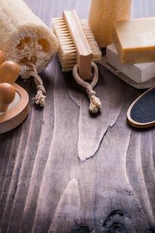 Pezzo di bagno massaggiatore spugnetta nailbrush saponetta su tavola di legno d'epoca con poco copyspace