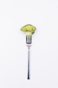 Pezzo di broccoli freschi sulla forcella isolato su superficie bianca