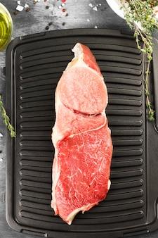 Pezzo di carne cruda di manzo su una griglia con pepe, olio d'oliva e un timo