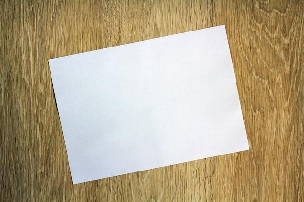 Pezzo di carta bianco in bianco su legno