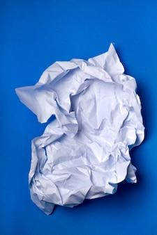 Pezzo di carta bianco rugoso su uno sfondo blu.