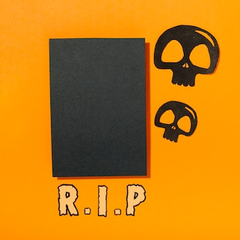 Pezzo di carta nero con teschi e iscrizione ri p
