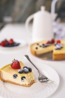 Pezzo di cheesecake casalingo della bacca di inverno di natale su un piatto bianco