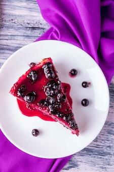 Pezzo di cheesecake sul piatto bianco con ribes su legno colorato. vista dall'alto.