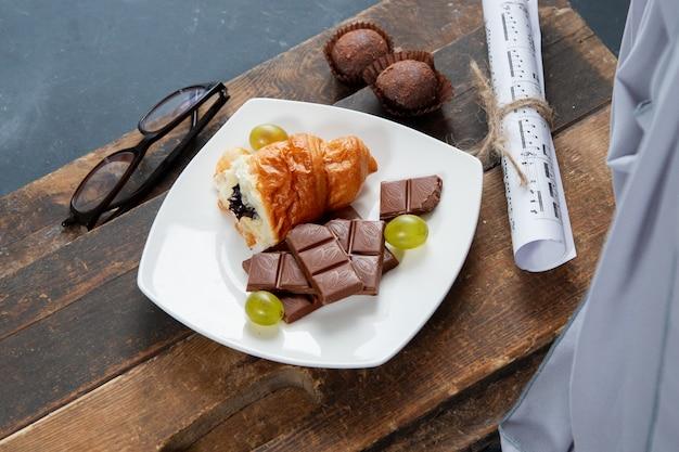 Pezzo di cornetto e barretta di cioccolato in un piatto bianco sulla tavola di legno