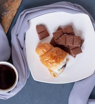 Pezzo di cornetto e barretta di cioccolato in un piatto bianco