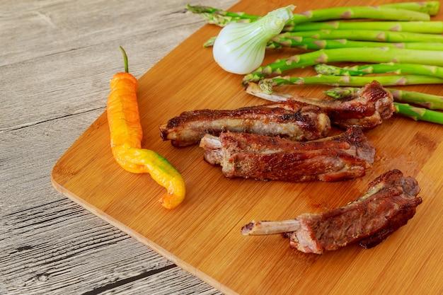 Pezzo di costolette di carne di vitello al forno glassato fresco sotto salsa dolce con pomodori hot chili pepper rosa