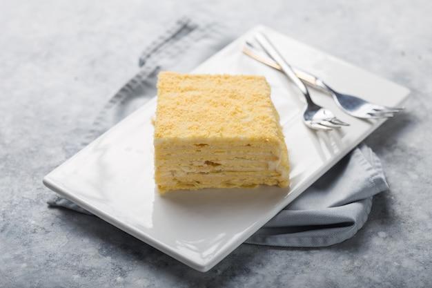 Pezzo di dolce napoleone sul piatto bianco su sfondo concreto, vista da vicino. dolce tradizionale millefoglie con pasta sfoglia e crema pasticcera, copia spazio.