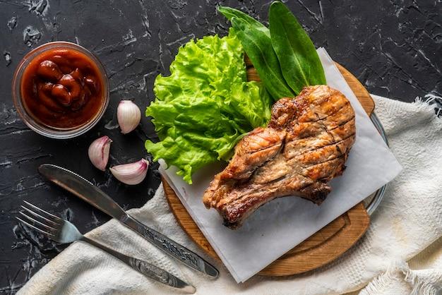 Pezzo di filetto di maiale arrosto cucinato con foglie di lattuga, cipolla e salsa, carne spazzatura