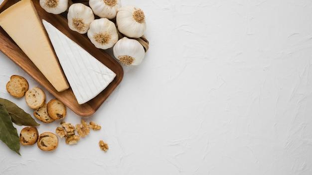 Pezzo di formaggi su vassoio di legno con foglie di alloro; fetta di pane; bulbo di noce e aglio su superficie bianca