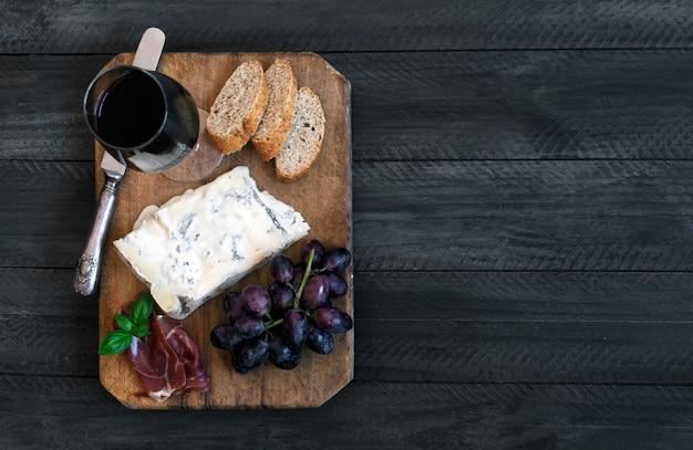 Pezzo di formaggio blu spagnolo su un vecchio tagliere di legno