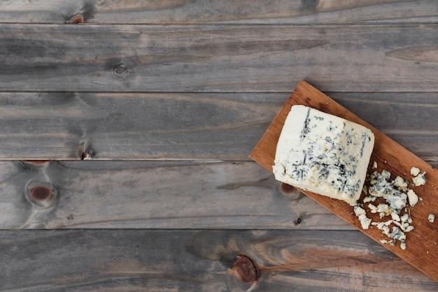 Pezzo di formaggio roquefort su tavola di legno sopra la scrivania