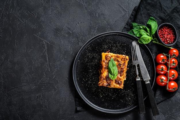 Pezzo di gustosa lasagna calda. cibo italiano tradizionale. muro nero. vista dall'alto. spazio per il testo