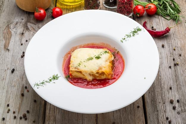 Pezzo di gustose lasagne calde con vino rosso.