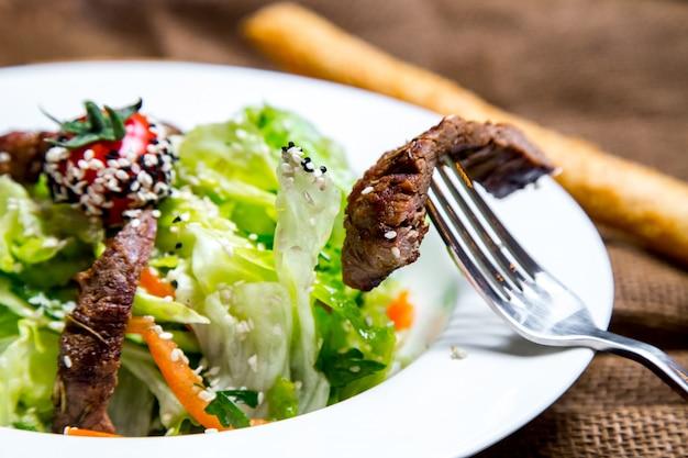 Pezzo di insalata di carne sulla vista laterale folk