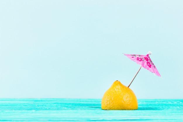 Pezzo di limone giallo con ombrello rosa in alto su sfondo blu