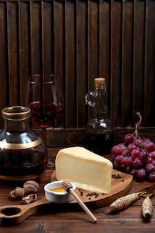 Pezzo di parmigiano servito con uva e vino