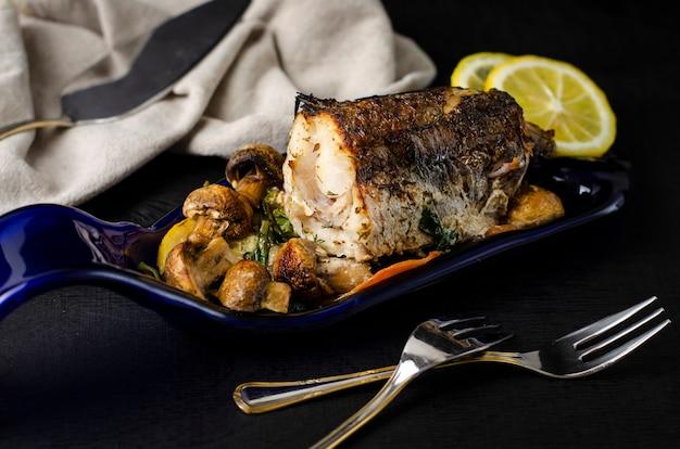 Pezzo di pesce al nasello al forno con verdure su un piatto blu fatto dalla bottiglia