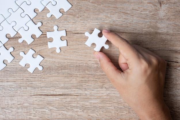 Pezzo di puzzle collegamento mano uomo d'affari. soluzioni aziendali, obiettivi della missione, successo, obiettivi, cooperazione, partenariato e strategia