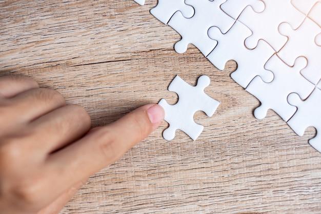 Pezzo di puzzle collegamento mano uomo d'affari. soluzioni aziendali, obiettivo della missione