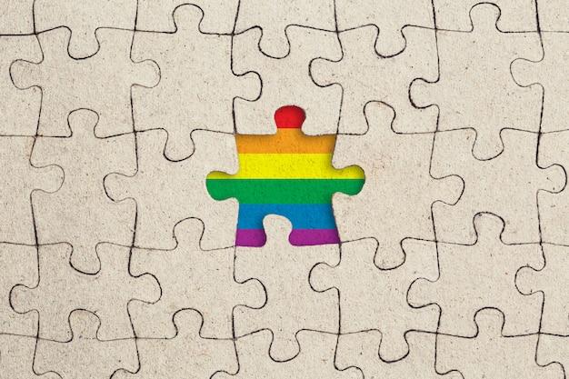 Pezzo di puzzle e bandiera arcobaleno