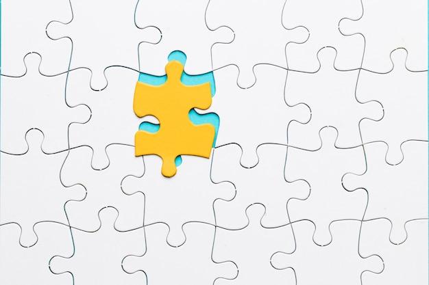 Pezzo di puzzle giallo con puzzle di griglia bianca