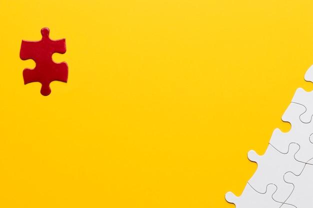 Pezzo di puzzle rosso in piedi separatamente dal pezzo di puzzle bianco su sfondo giallo