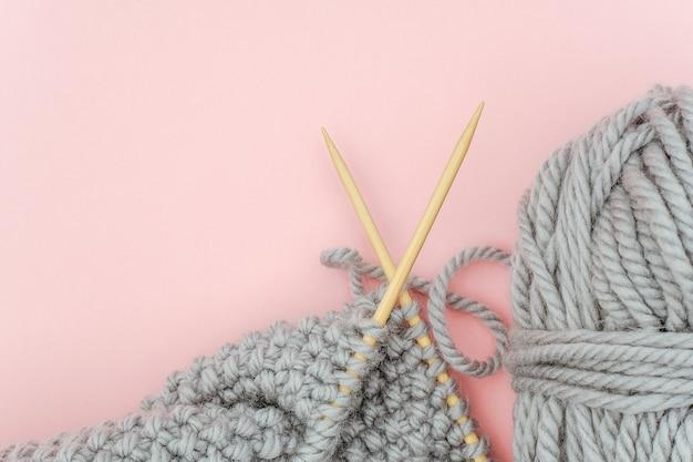 Pezzo di tessuto a maglia grigio su aghi di legno di bambù con gomitolo di lana su sfondo rosa