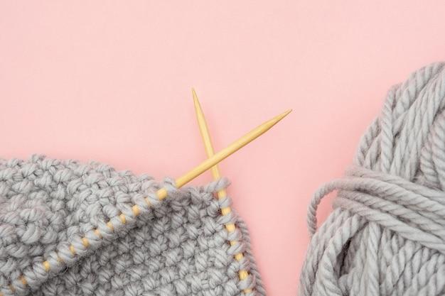 Pezzo di tessuto a maglia grigio su aghi di legno di bambù con gomitolo di lana