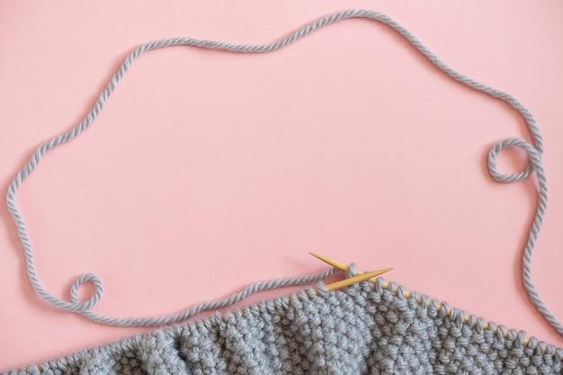 Pezzo di tessuto a maglia grigio sugli aghi, processo di lavoro a maglia su sfondo rosa.