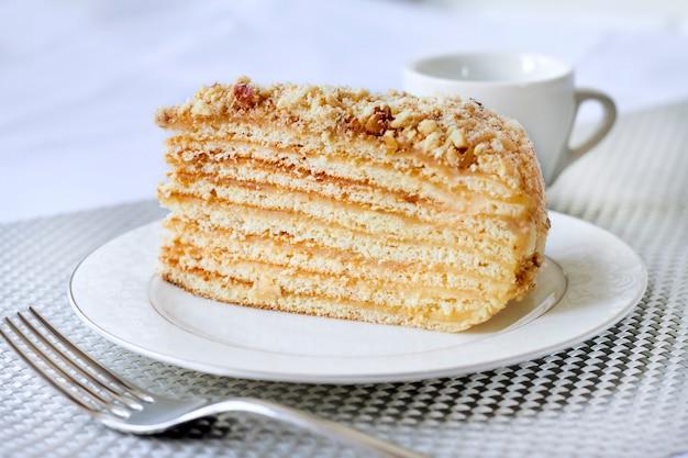 Pezzo di torta a strati con crema pasticcera e noci su un piatto