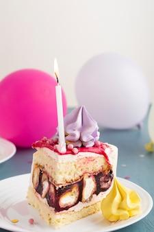 Pezzo di torta con candela e palloncini