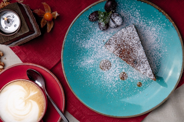 Pezzo di torta di carote, ricoperta di zucchero a velo in un piatto blu su un tovagliolo rosso con una tazza di caffè e zucchero di canna