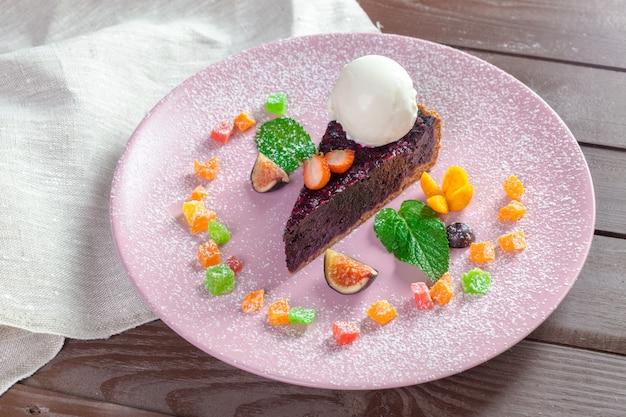 Pezzo di torta di farina di mais e mandorle al cioccolato con pioviggine balsamico e gelato