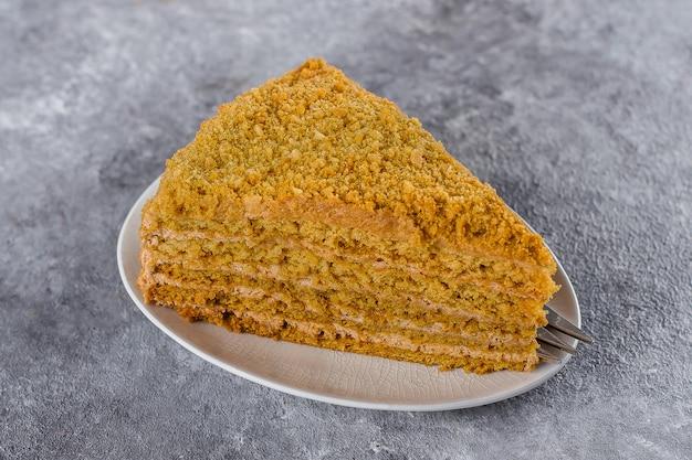 Pezzo di torta di miele fatta in casa su un piatto e una tazza di tè su uno sfondo grigio cemento