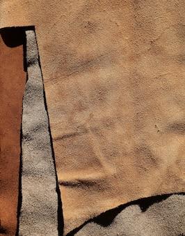 Pezzo di vera pelle marrone sullo sfondo del tessuto