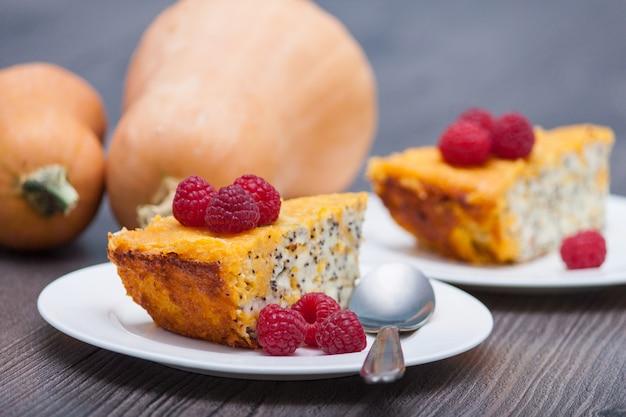 Pezzo di zucca cheesecake fatta in casa con lamponi, papavero sul tavolo di legno. salutare