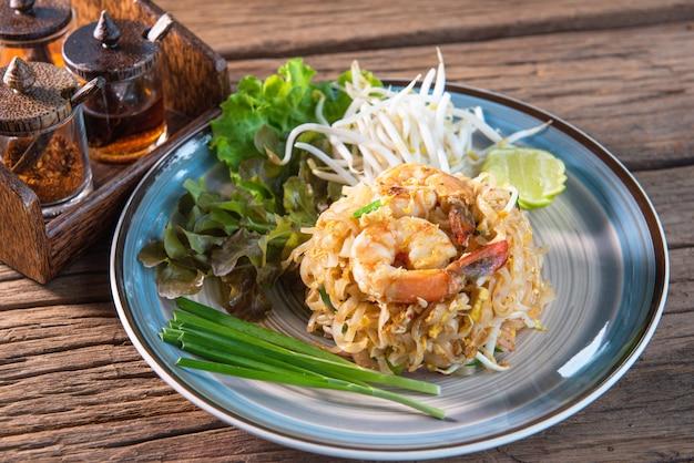 Phad thai con gamberi freschi, aggiungere le uova, servito con lattuga, germogli di soia, cipollotti, con contorno