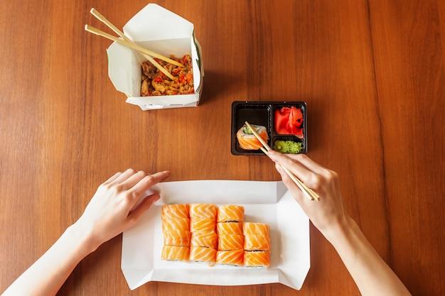 Philadelphia rotola con riso sul tavolo. salmone, formaggio philadelphia, cetriolo, avocado, bastoncini di legno sulle mani.