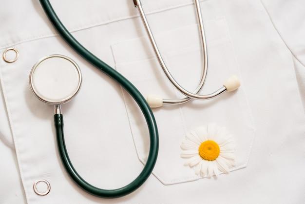 Phonendoscope medico su una vestaglia medica. una mela verde è un fiore margherita. concetto di salute