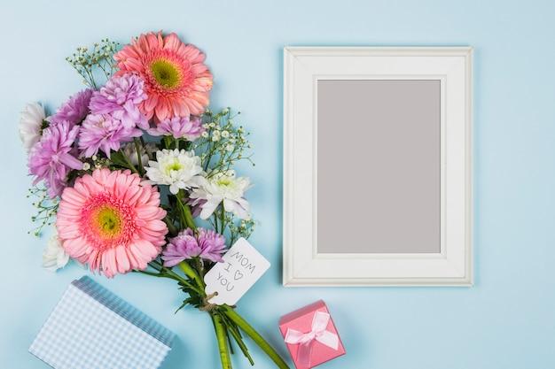 Photo frame vicino a fiori freschi con titolo sull'etichetta vicino pacchetto, presente e notebook