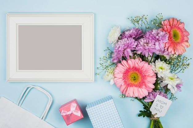 Photo frame vicino bouquet di fiori freschi con titolo su tag vicino pacchetto, presente e notebook