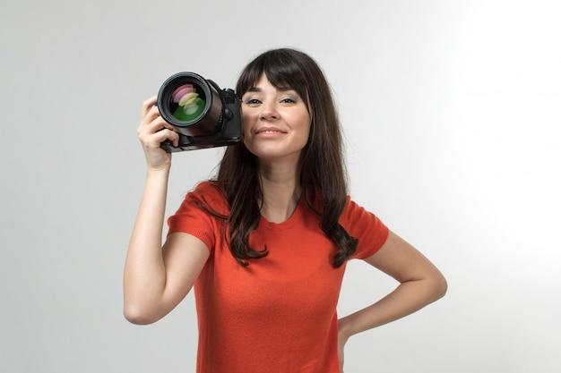 Photocamera sorridente della tenuta della giovane signora in maglietta progettata di buon umore con capelli lunghi su bianco
