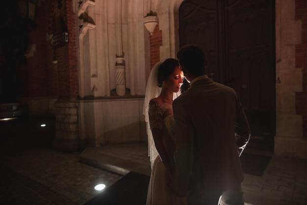 Photosession notturno degli sposi a cracovia, gli sposi camminano intorno alla chiesa