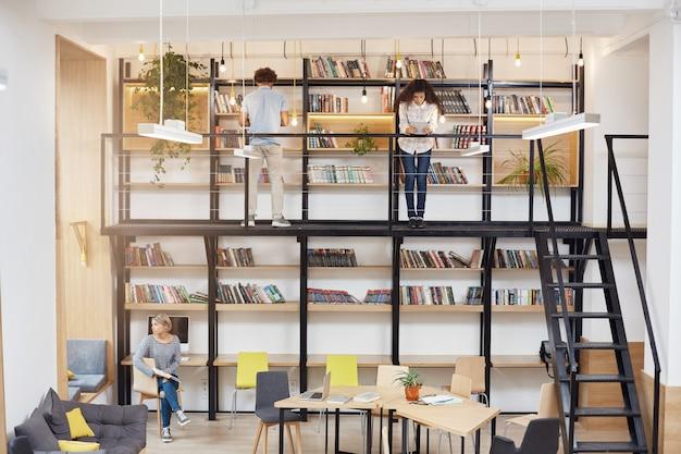 Phto della grande biblioteca moderna di unità. ragazza bionda che si siede sul chear che osserva nella finestra con l'espressione vaga del fronte. due giovani in piedi vicino a scaffali, libri di lettura.