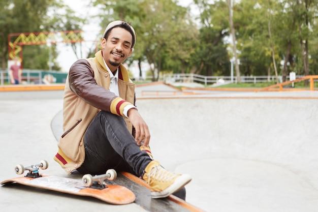 Piacevole skateboarder alla moda fa la sua cosa preferita, si riposa dopo un lungo allenamento all'aperto,